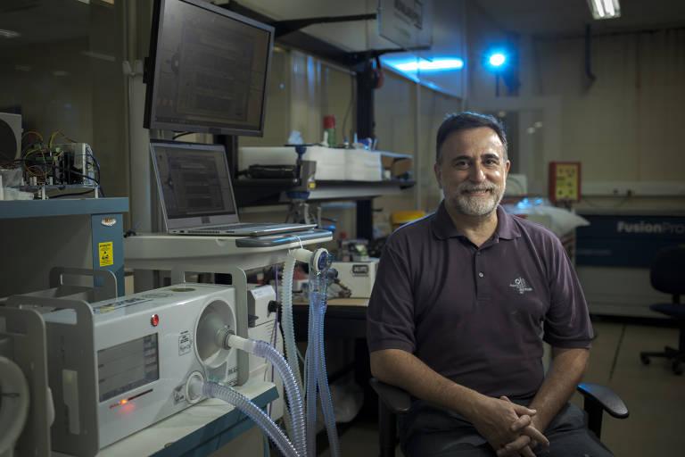 Homem sentado em oficina, ao lado de equipamento com tubos