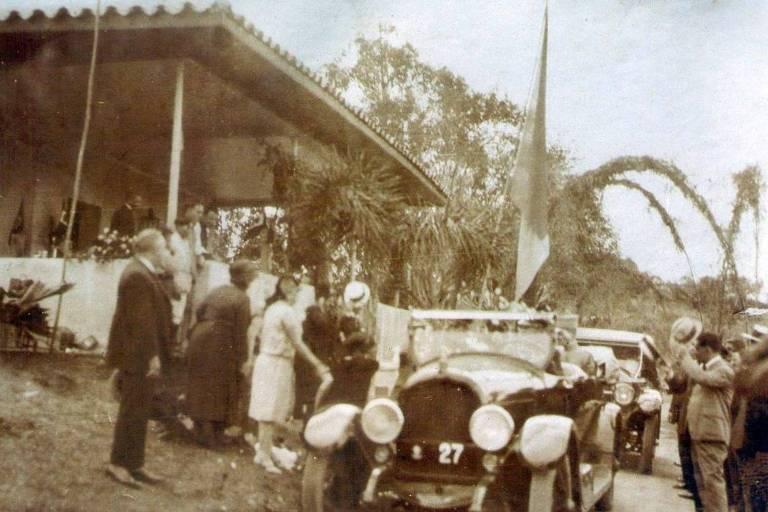 Foto antiga de carros passando em estrada e pessoas ao lado
