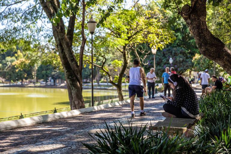 Moça sentada em banco e pessoas andando em parque, com lago ao lado