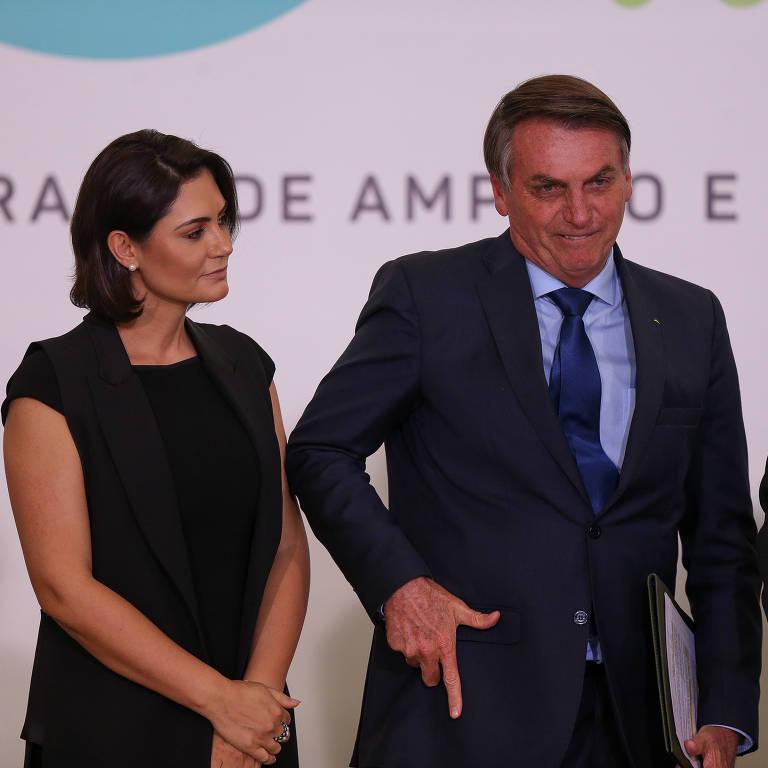 O presidente Jair Bolsonaro, ao lado da primeira-dama, Michelle Bolsonaro, faz gesto de arma com a mão