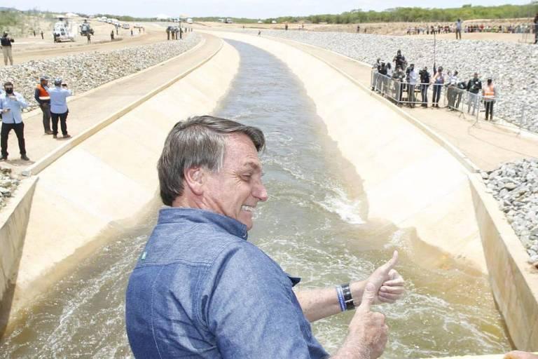 Bolsonaro está de camisa azul; ele está de perfil direito, sorrindo e fazendo joinha com as mãos; ao fundo, fluxo de água da transposição e pessoas