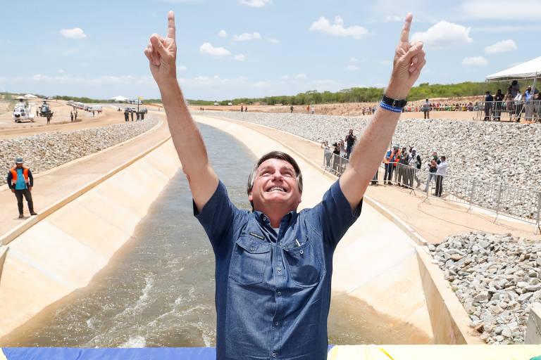 Bolsonaro está com os braços levantados e os dedos indicadores apontando para o céu. Está olhando para cima. Ele é um homem branco de cabelos lisos e castanhos, com alguns fios grisalhos. Veste uma camisa azul. Ao fundo Rio São Francisco em transposição.