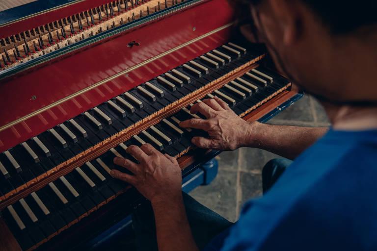 homem de costas de camiseta azul com as mãos sobre teclados de um instrumento que tem duas linhas de teclados, uma sobre a outra, de teclas pretas