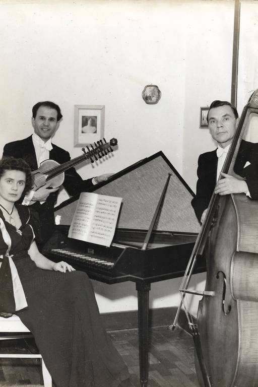 mulher sentada a uma espineta, no fundo homem com violino e à frente homem com baixo acustico