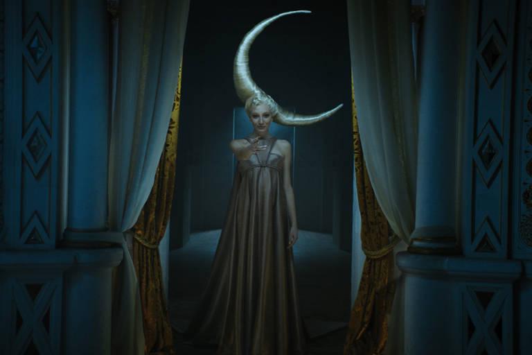 mulher com enorme acessório em forma de lua na cabeça
