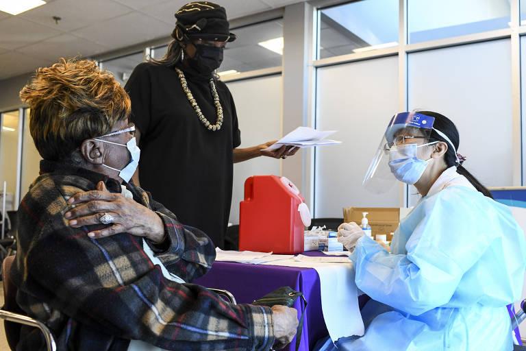 Moradora de Washington fala com enfermeira antes de ser vacinada, após conseguir horário com priorização de bairros mais atingidos