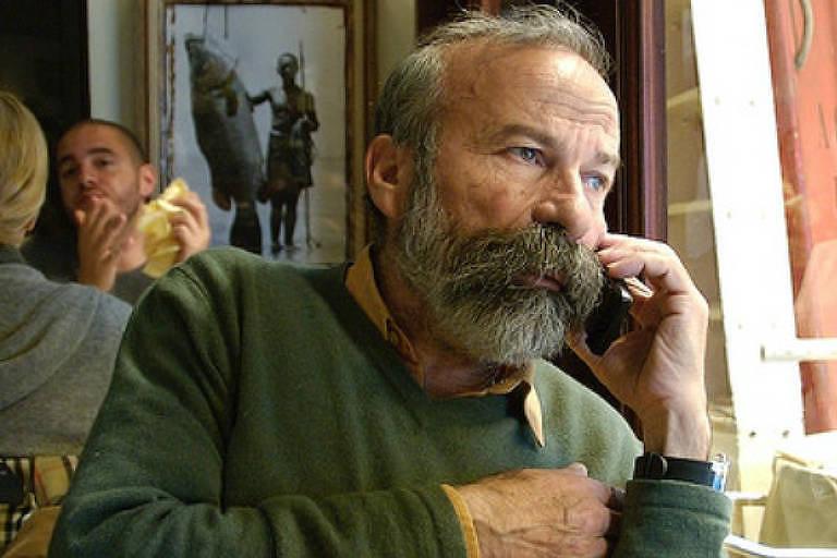 homem de barba e cabelos brancos falando ao telefone proximo de uma janela no que parece ser um restaurante