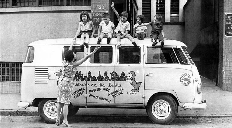 Equipe mirim de reportagem em cima da Kombi da Folhinha; veículo branco e amarelo seguia as cores do restante da frota do jornal e tinha estampados os nomes das seções do suplemento infantil, servindo de apoio para reportagens