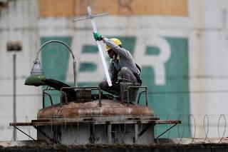 A worker checks the fuel volumes on a train wagon near a tank of Brazil's state-run Petrobras oil company in Brasilia