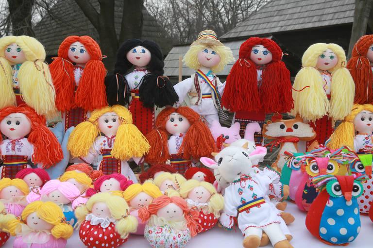 Imagem mostra bonecas de pano coloridas, com cabelos de lã, expostas em feira