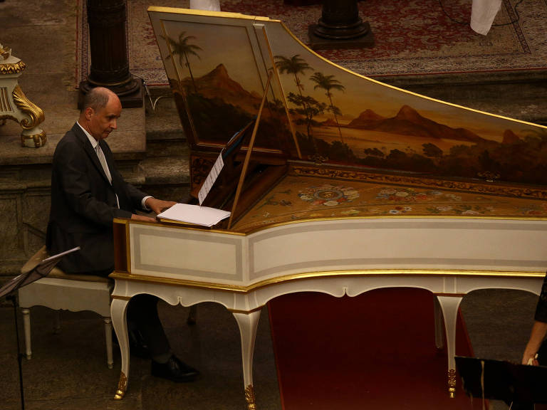 homem sentado a instrumento musical de teclado com ampla cauda, o móvel é branco com detalhes em dourado e pinturas na decoração