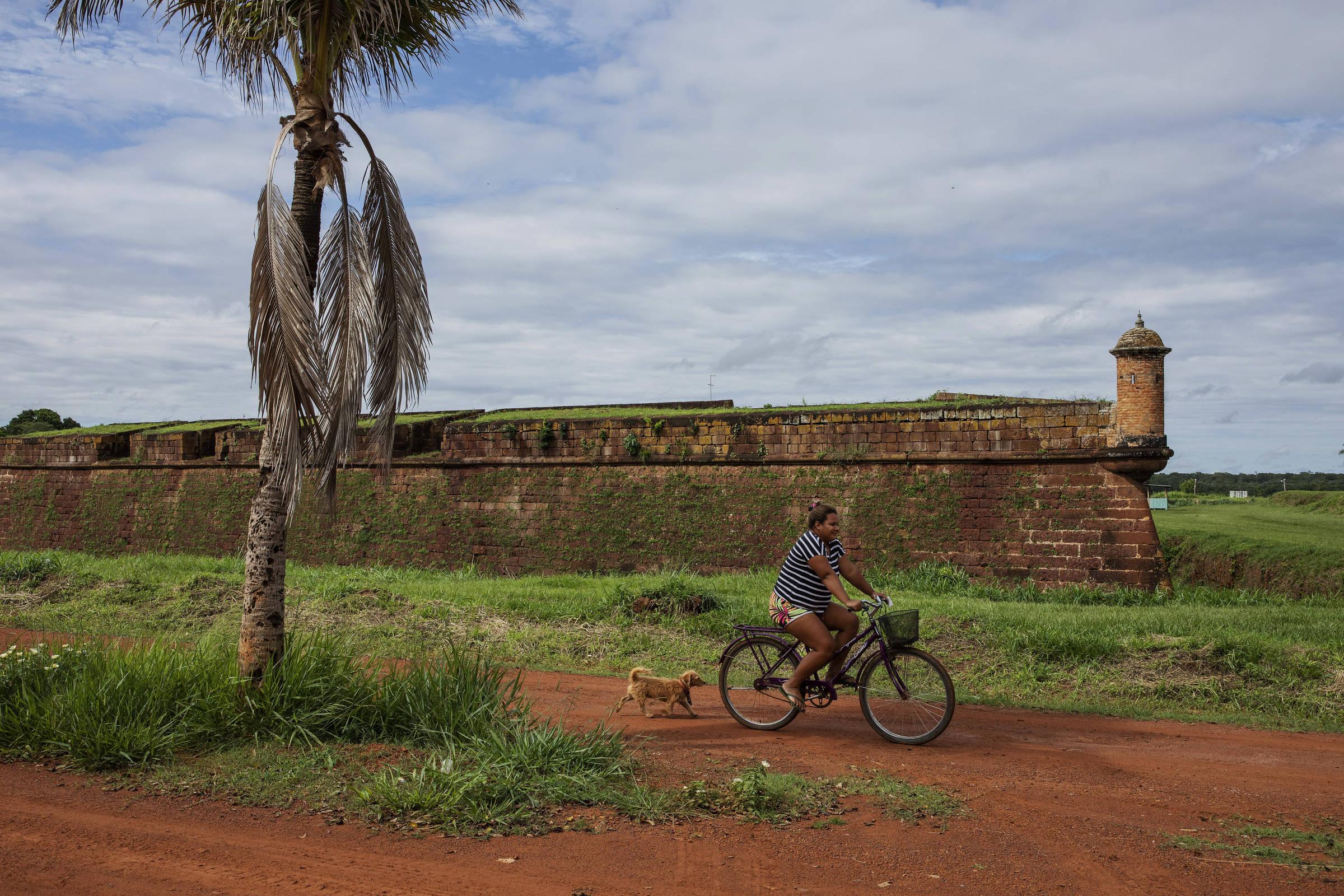 Morador da comunidade quilombola do Forte Príncipe da Beira, no vale do rio Guaporé, em Rondônia, passa de bicicleta em frente a fortaleza militar construída no século 18