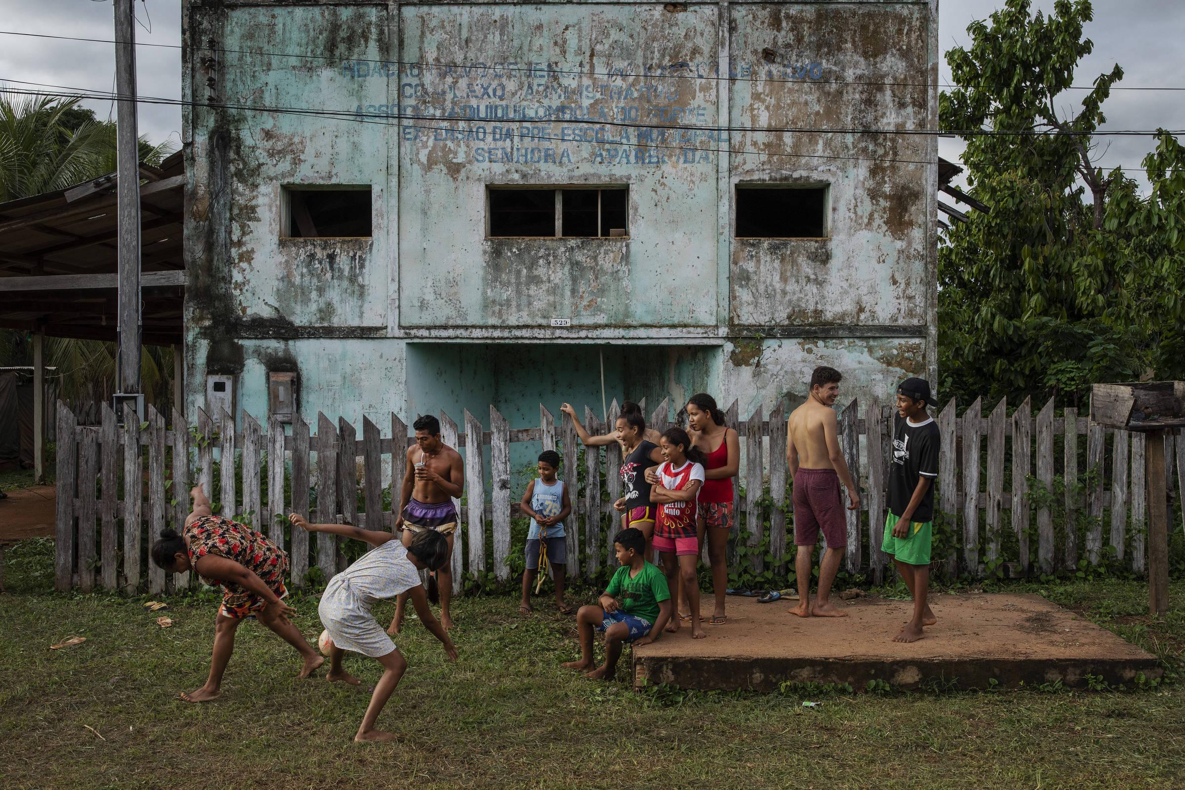 Crianças da comunidade quilombola do Forte Príncipe da Beira assistem a um jogo de futebol em frente à antiga sede da associação da comunidade