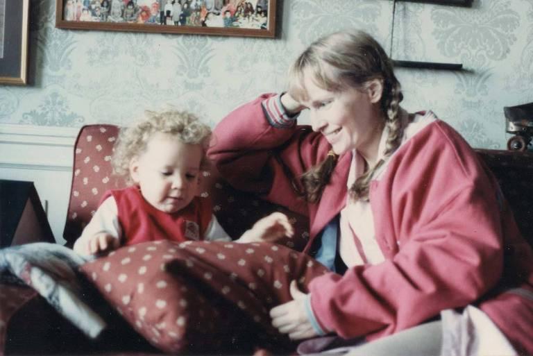 mulher loira sorri para bebê loiro sentado no sofá