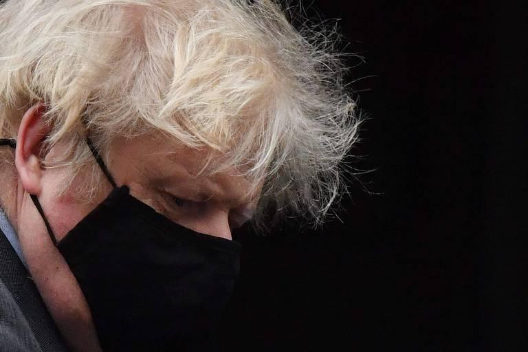 Boris com os cabelos loiros bem desgrenhados e uma máscara preta, de perfil
