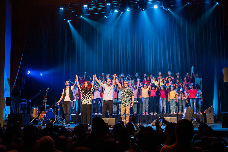 Um palco lotado de pessoas, onde à frente se veem adultos, e atrás, sobre um platô, um coro formado por crianças
