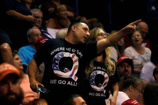 FILE PHOTO: Supporters wearing shirts with the QAnon logo, chat before U.S. President Donald Trump takes the stage during his Make America Great Again rally in Wilkes-Barre