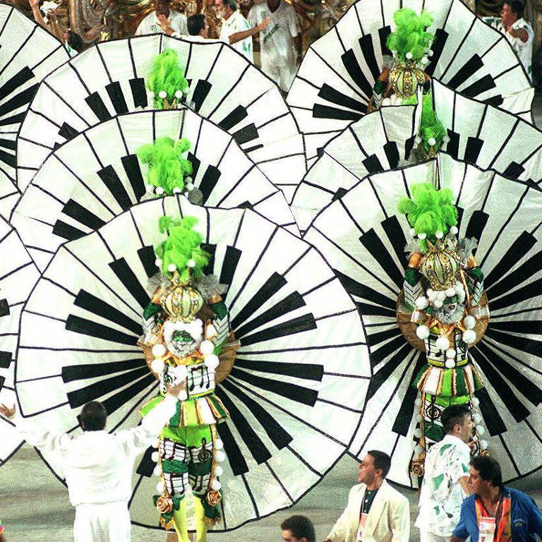 dois homens, no primeiro plano, com roupas de fantasia de carnaval nas cores preto, branco e verde limão, eles estão de braços abertos com longos panos que representam as teclas de um piano e é possível ver que atrás deles há outros