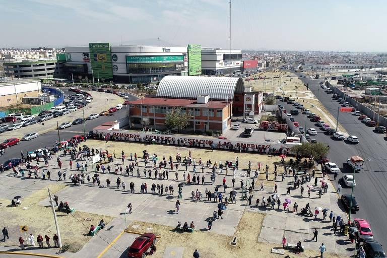 Imagem aérea mostra três longas filas espaçadas em praça