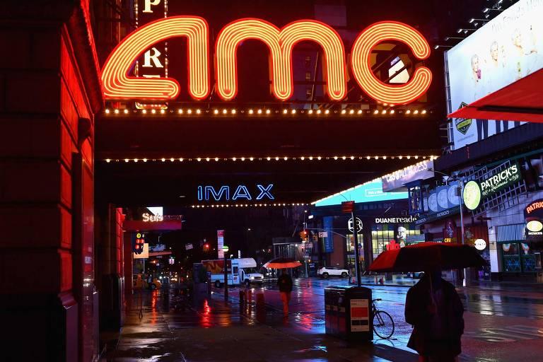"Rua a noite. Luzes iluminam letreiro onde se lê ""AMC"""