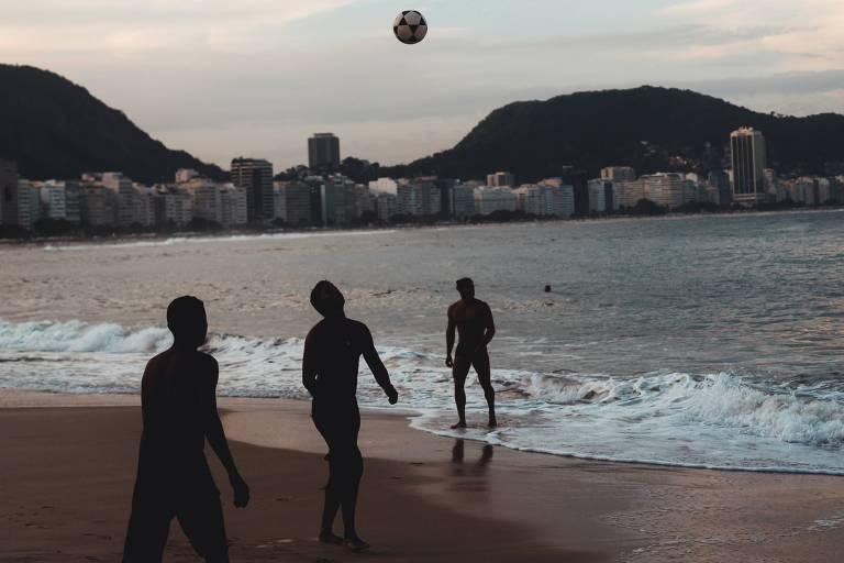 Jovens jogam futebol em praia do Rio de Janeiro
