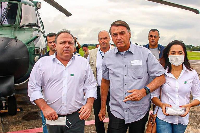 Bolsonaro, Pazuello e a senadora desembarcam de um helicóptero. Os dois não usam máscara, assim como outras pessoas da comitiva, que segue atrás