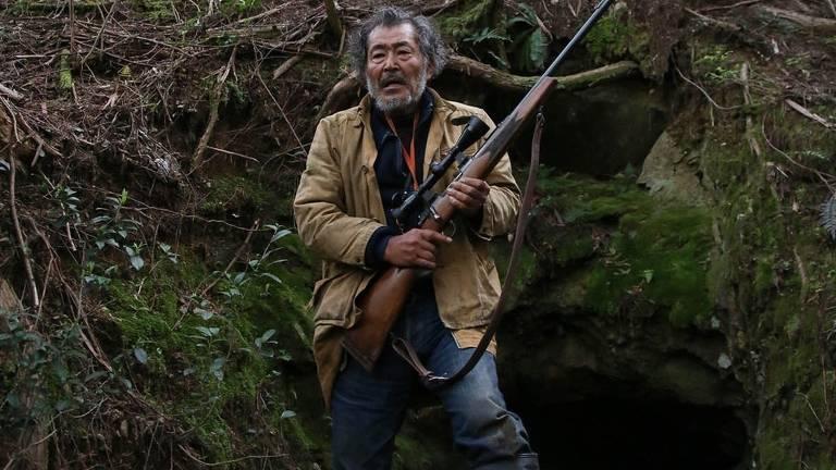 homem com arma em meio à floresta