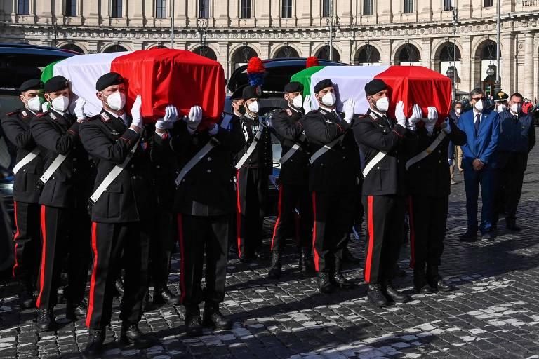Guardas em vestes cerimoniais carregam dois caixões cobertos em bandeiras da Itália