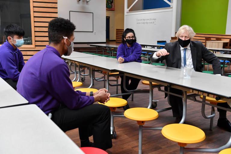 O primeiro-ministro Boris Johnson está sentado em uma mesa e gesticula enquanto fala com estudantes que também estão sentados; todos usam máscara e estão distanciados