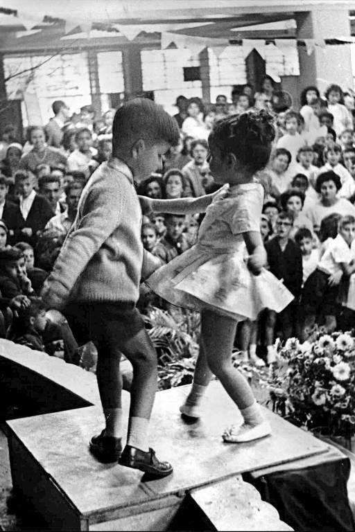 crianças pequenas dançam em um palco diante de um salão lotado de pessoas