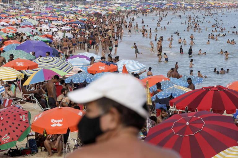 Banhistas em praia lotada de pessoas e guarda-sóis com um senhor de máscara e boné em primeiro plano.