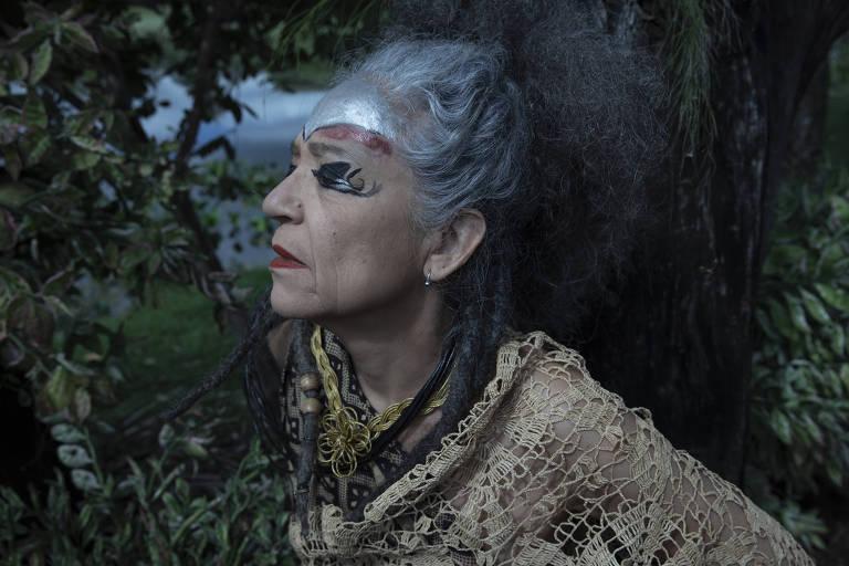 A cantora Alzira E de perfil, com vegetação ao fundo