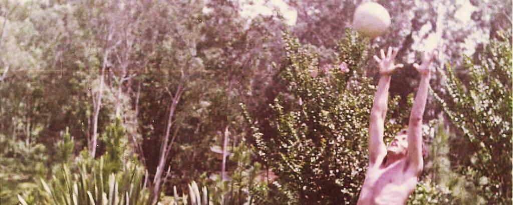 homem de sunga captura bola no ar