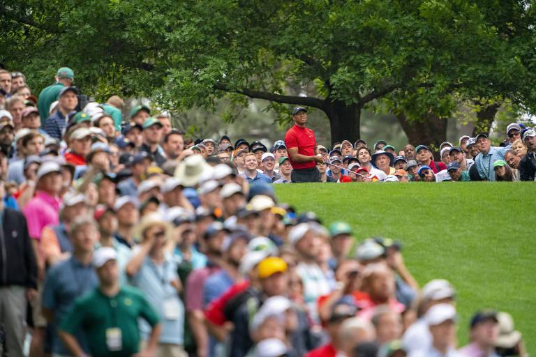 Foto mostra público majoritariamente de pessoas brancas em volta do campo, e Tiger Woods ao fundo, vestido de vermelho, após uma tacada