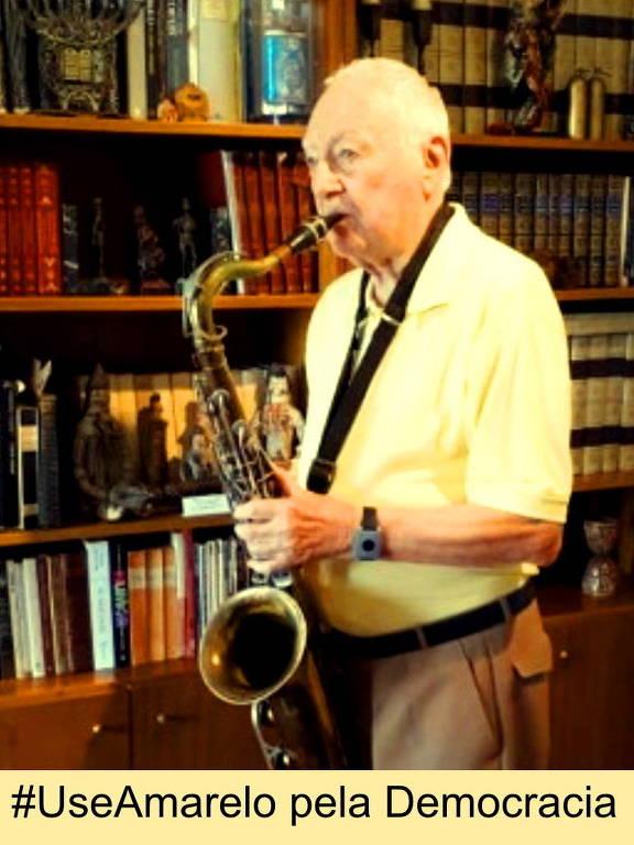 O leitor Moisés Spiguel, 90, praticando saxofone e usando amarelo em homenagem à campanha da Folha pela democracia