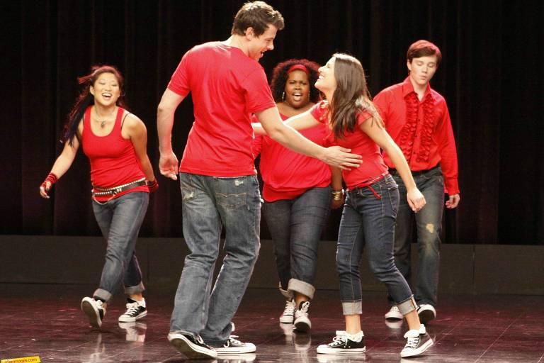 Cinco adolescentes com camisetas vermelhas cantam a dançam num palco