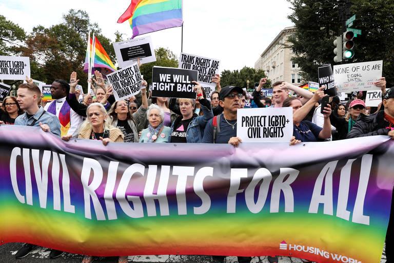 manifestantes seguram bandeiras com as cores do movimento e cartazes com frases como 'direitos civis para todos'