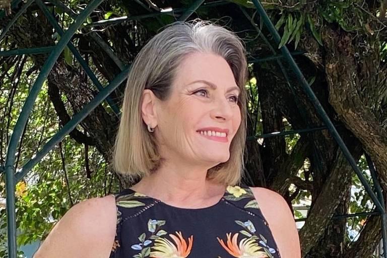 Mulher sorri, de cabelo branco nos ombos e vestido preto florido