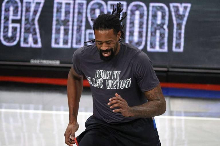 """O jogador Andre Jordan, do Brooklyn Nets, se aquece usando camiseta escrita: """"Construído pela história negra"""". As camisetas fazem parte da celebração do Black History Month nos jogos da NBA"""