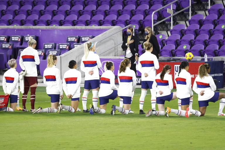 Jogadoras vestidas de branco, azul e vermelho, algumas ajoelhadas e outras de pé