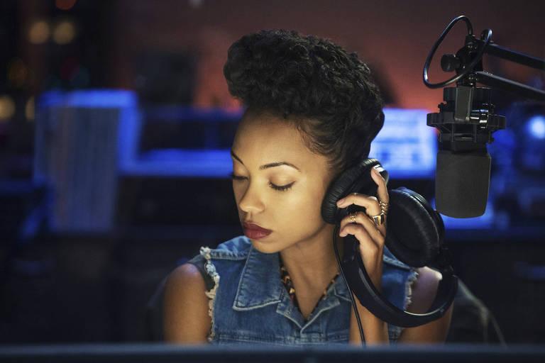 Mulher negra com fone de ouvido em estúdio
