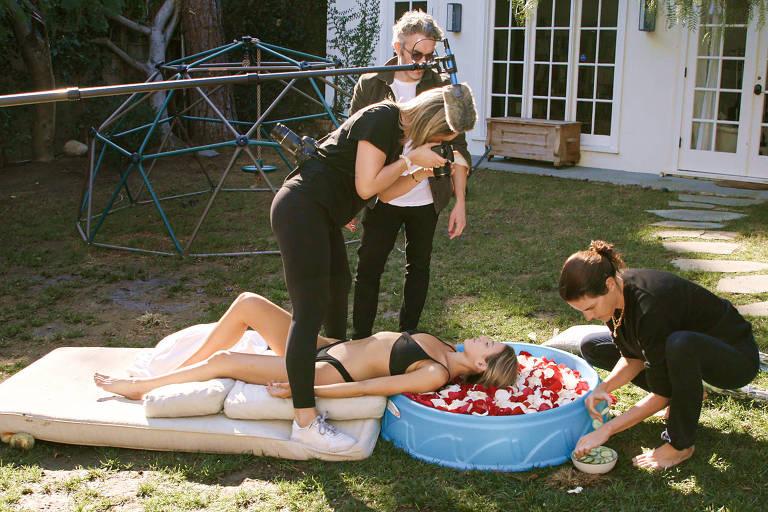 mulher com a cabeça apoiada em bacia com pétalas de rosa é fotografada por time de profissionais