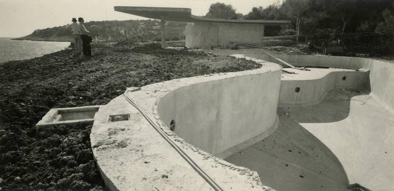 Foto preto e branco mostra paredes curvas de concreto sendo construídas num terreno, onde a terra está remexida; ao fundo, uma construção também curvilínea já está pronta e, do lado esquerdo, dois homens não identificados observam o canteiro de obras
