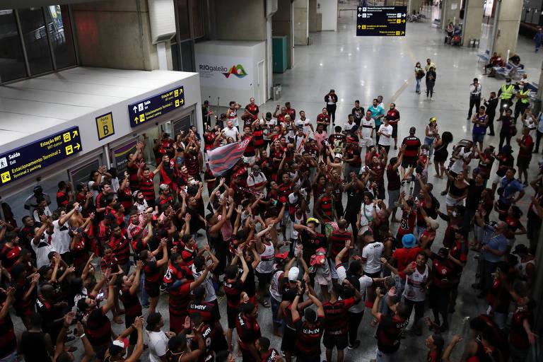 Torcedores do Flamengo se aglomeram no aeroporto Internacional do Galeão, no Rio de Janeiro, para receber o time campeão brasileiro