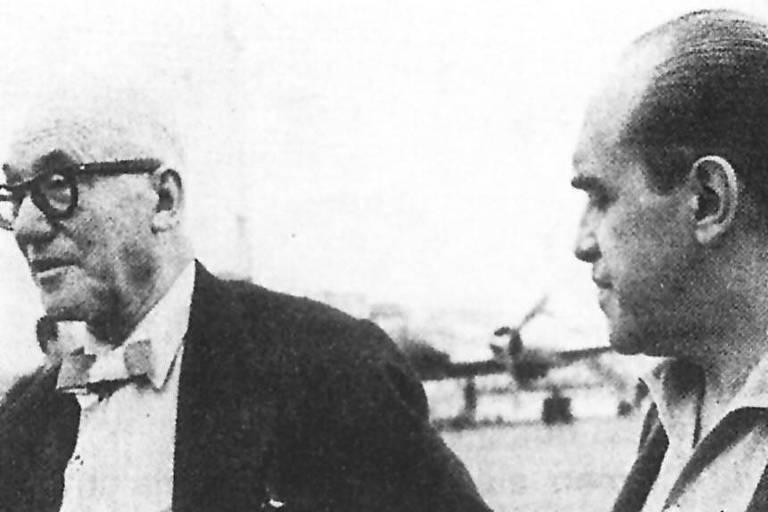 foto preto e branca mostra Le Corbusier (à esq.) e Niemeyer; os arquitetos trabalharam juntos em projetos no Brasil e nos EUA; Le Corbusier usa paletó e gravata borboleta, é calvo e tem óculos redondos, enquanto Niemeyer, bem mais jovem, usa camisa com paletó sem gravata; ao fundo vê-se um avião