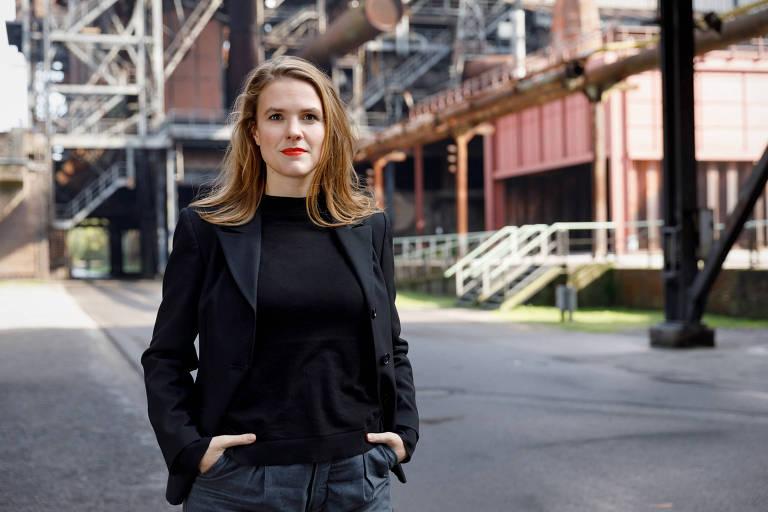 Moça de cabelos castanhos lisos na altura do ombro, de camiseta e paletó preto, com as mãos no bolso, posa em frente a prédios, na rua
