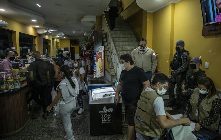 Fiscais da vigilância sanitária, com colete marrons e máscaras, estão dentro de um bar cheio