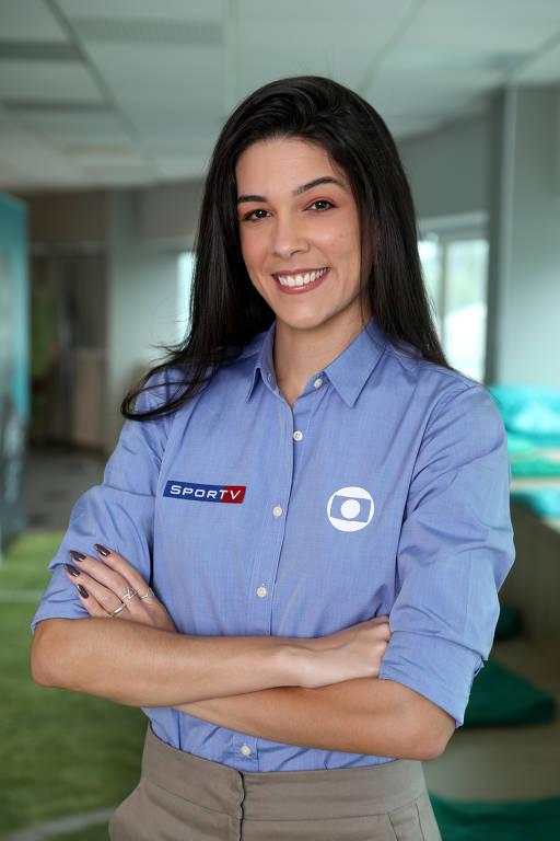 mulher de braços cruzados de cabelos escuros lisos e longos usando camisa azul