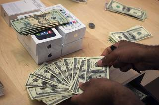 A cashier counts U.S. dollars next to five new Apple iPhone 5S phones at the Apple Retail Store on Fifth Avenue in Manhattan, New York
