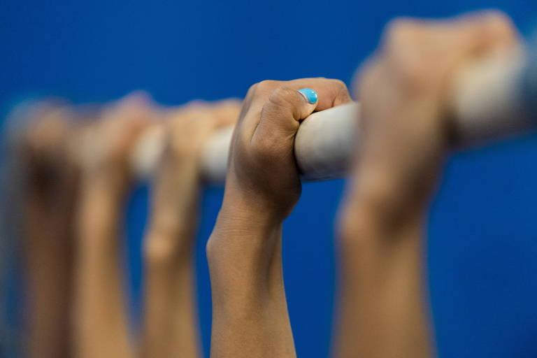 Cinco mãos seguram uma barra usada nas competições de ginástica